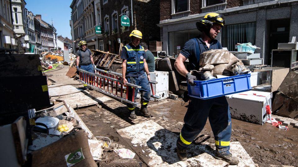 Helfer tragen Leiter durch Straße