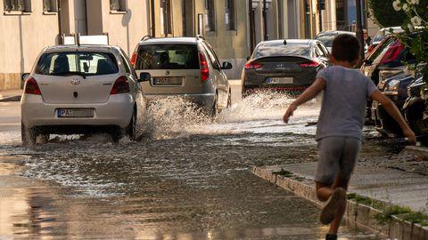 Kind läuft über überflutete Straße