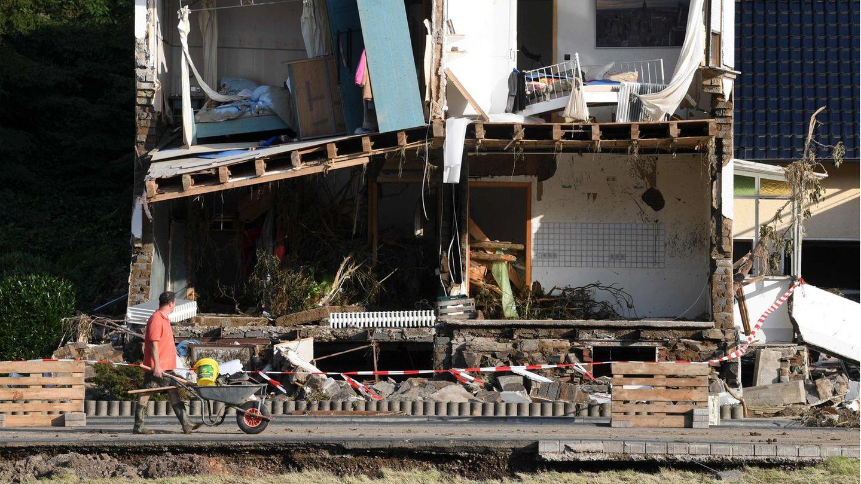 Ein Mann schiebt eine Schubkarre an einem zerstörten Haus vorbei