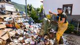 Ahrbrück, Rheinland-Pfalz:Ein Helfer lädt vom Hochwasser beschädigte Bücher mit einer Schubkarre auf einem Haufen ab.