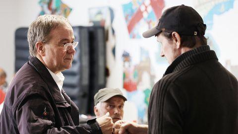 Armin Laschet (l.) spricht mit einem Erftstädter in einer Notunterkunft