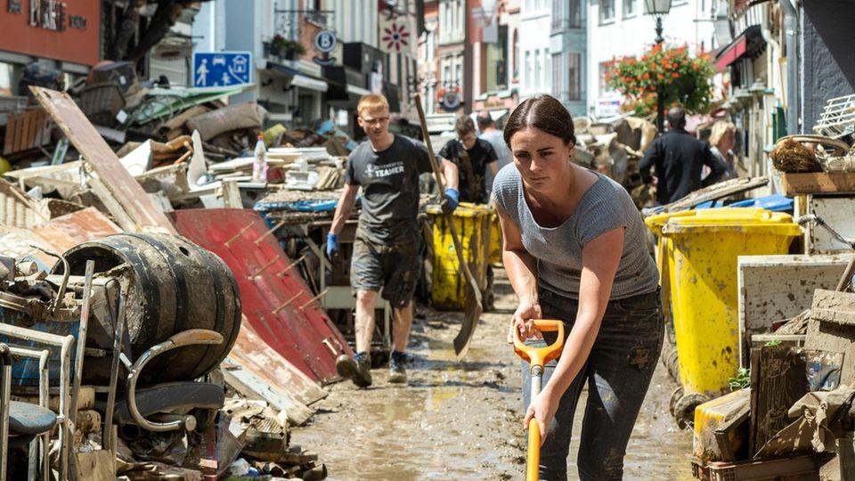 Mit einem Schneeschieber reinigt eine weiße Frau in Gummistiefeln eine Straße von schlammigem Wasser - oder versucht es