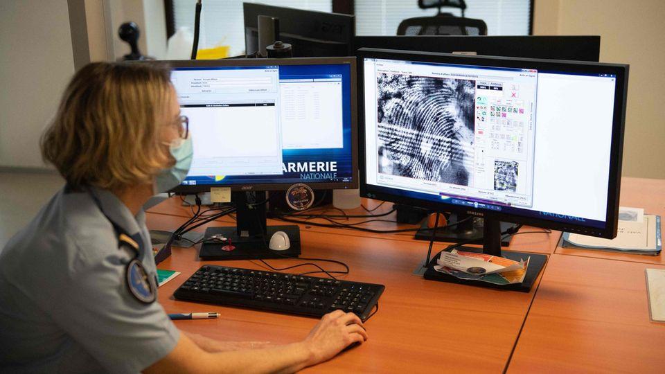 Eine weiße Frau mit blonden, schulterlangen Haaren und einer kurzärmeligen, hellblauen Uniform schaut auf zwei Monitore