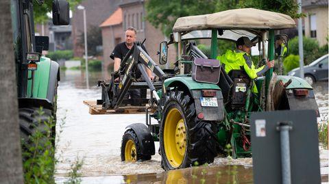 Zwei Männer fahren mit einem Traktor durch eine überflutete Straße in Ophoven