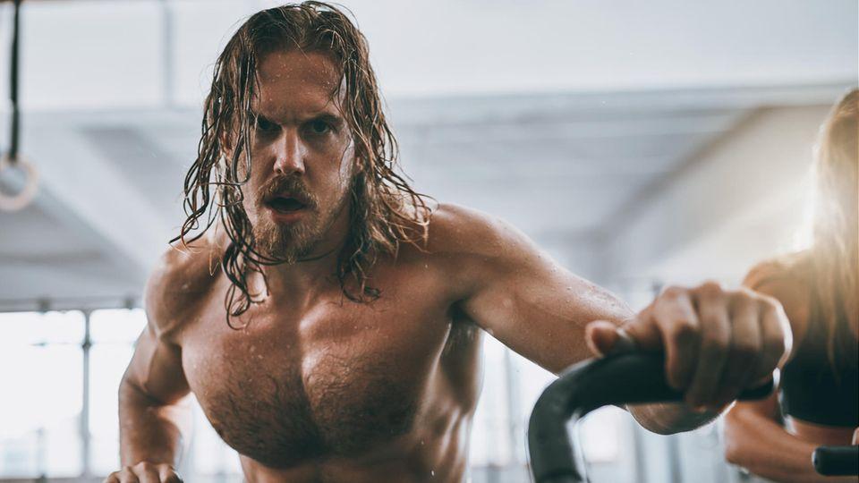Ein Mann mit nacktem Oberkörper trainiert im Fitness-Studio