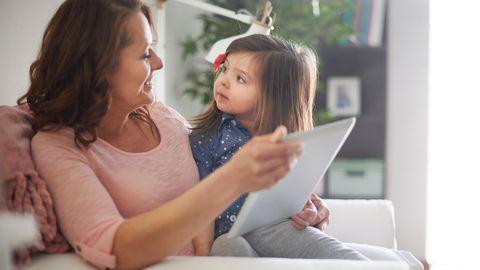 Kind schaut Mutter fragend an, während sie sich gemeinsam etwas auf einem Tablet anschauen