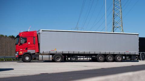 Ein roter Lkw mit silbergrauem Auflieger steht auf einem Rastplatz in der Sonne. Dahinter die Hecks weiterer Auflieger