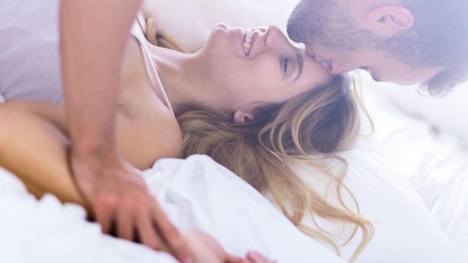 Ein Mann küsst eine Frau im Bett auf die Stirn