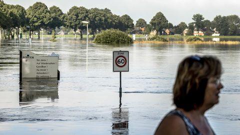 Niederlande, Arcen: Die Zufahrtsstraße zum Dorf Bergen steht am 18. Juli wegen des hohen Wasserstandes der Maas unter Wasser