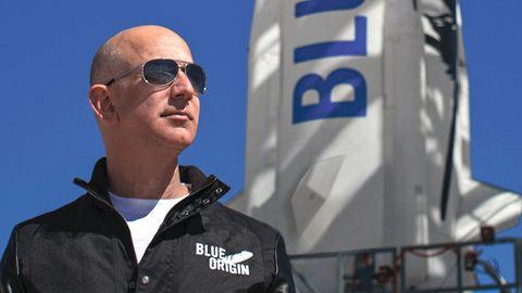 """Mit Sonnenbrille steht ein kahlköpfiger, weißer Mann vor einer weißen Rakete mit blauer """"Blue Origin""""-Schrift"""