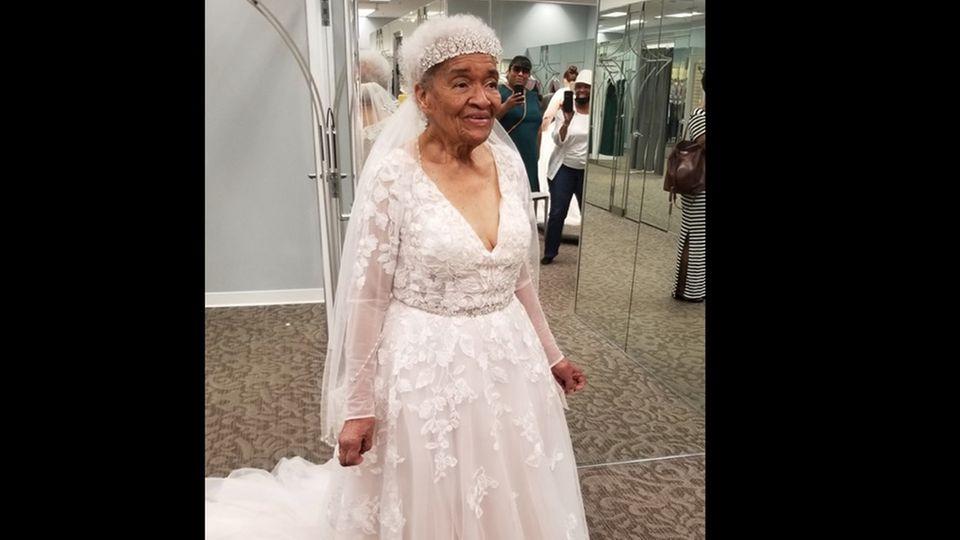 Martha Tucker guckt lächelnd in den Spiegel. Sie trägt ein weißes Brautkleid.