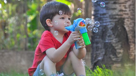Ein Kind hält eine Seifenblasenpistole in der Hand