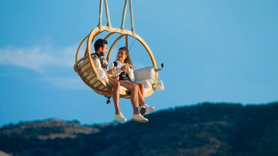 Maxime und Dario sitzen in einer Schaukel, die hoch über einem Kliff angebracht ist