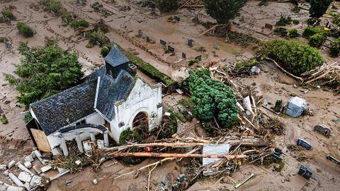 Aus der Luft ist eine weiße Kirche mit schwarzem Dach zu sehen, deren Friedhof voller Schlamm und angeschwemmte Bäume liegt