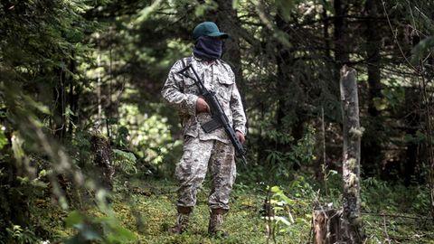 Im Tarnanzug mit Gesichtsmaske und bewaffnet mit einem Sturmgewehr patrouilliert ein Milizionär im Wald von Cherán
