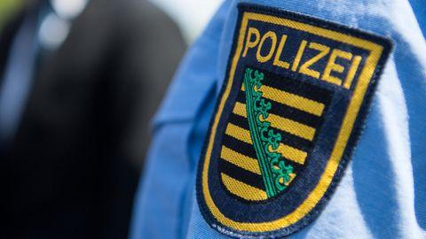 Das Logo der sächsischen Polizei ist an einer Polizeiuniform angebracht