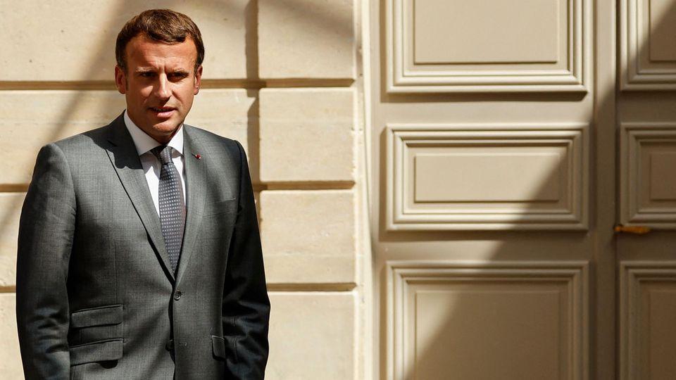 Emmanuel Macron steht vor einer massiven Holztür
