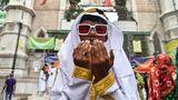 Ein junger Inder in weißem Gewand mit goldenen Bünden betet mit erhobenen Händen und trägt dabei eine weiße Sonnenbrille