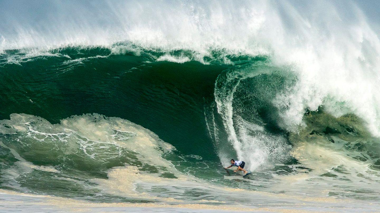 Ein Surfer erscheint sehr klein, während er eine Riesenwelle hinabsurft, von deren Kamm Gischt abweht