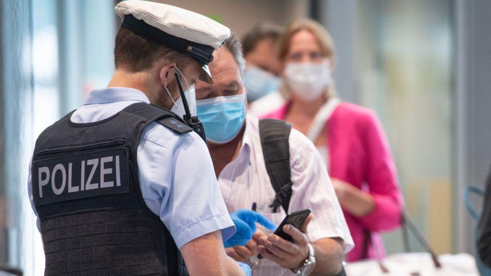 Einreisender zeigt einem Polizisten seinen digitalen Impfausweis