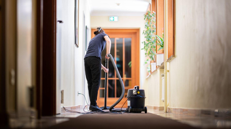Eine Frau saugt in einem Hotel einen Flur.
