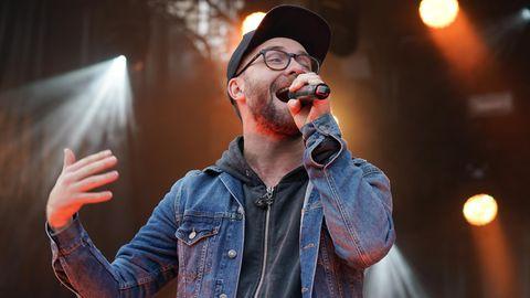 Mark Forster auf der Bühne mit Mikrofon in der Hand