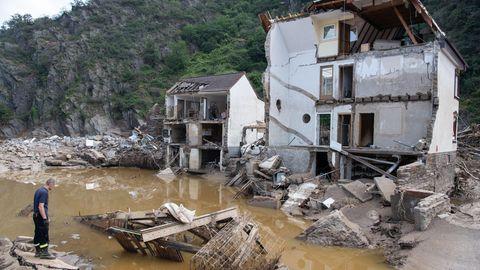 Ein Feuerwehrmann steht im Dorf Mayschoß vor einem völlig zerstörten Haus
