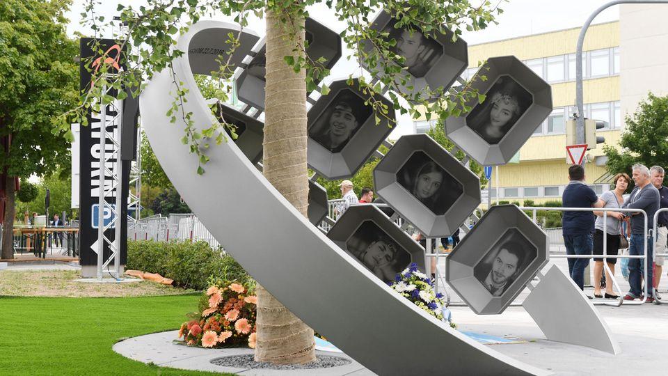 Das Mahnmal besteht aus einem Gingko-Baum, den ein zwei Meter hoher Edelstahlring, umfasst mit Fotos der Opfer