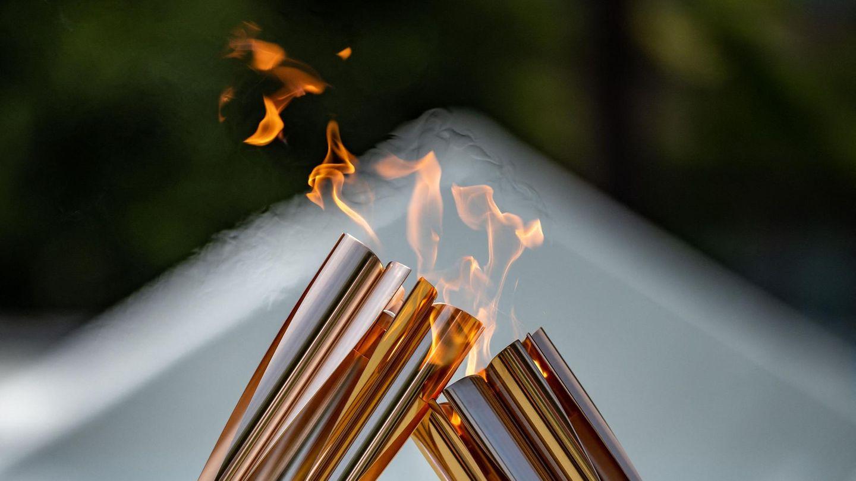 Zwei Fackeln reichen bei der Zeremonie im Hamacho Park in Nihonbashi naheTokio das olympische Feuer für bei einer Zeremonie weiter