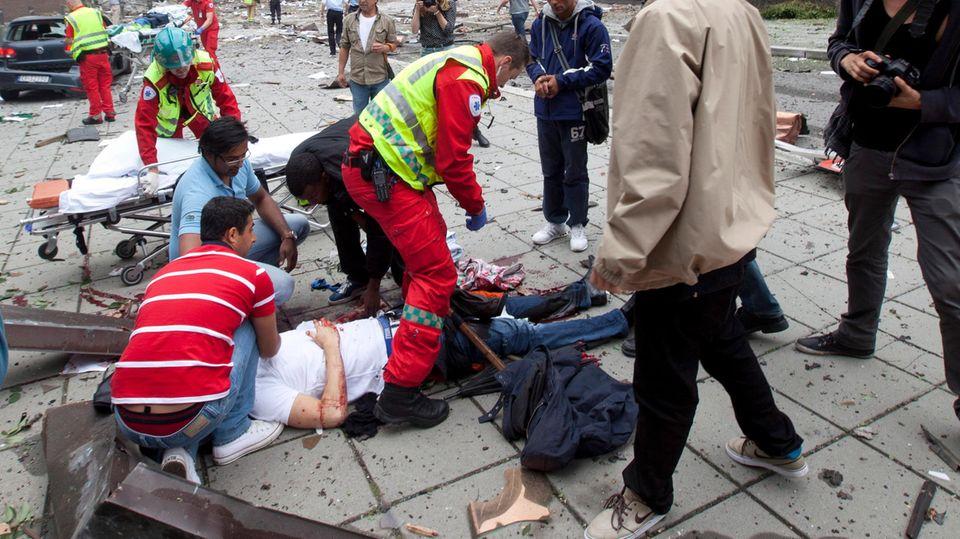 Rettungskräfte versorgen Verletzte in der Osloer Innenstadt nach der Bombenexplosion