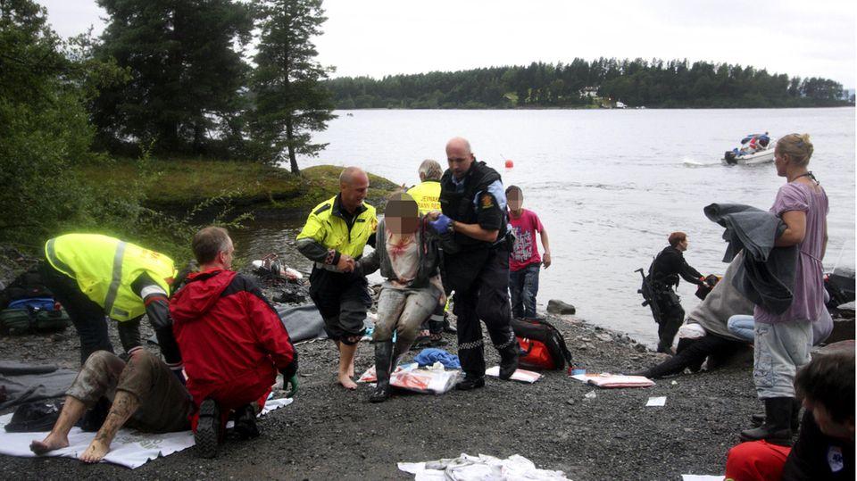 Polizisten, Rettungskräfte und Anwohner versorgen Verletzte, die von der InselUtøya gerettet wurden