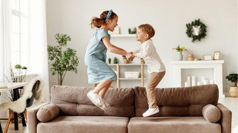 Mädchen und Junge springen auf Sofa