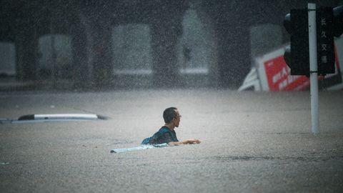 Ein Mann versucht eine überflutete Straße im chinesischen Zhengzhou zu überqueren