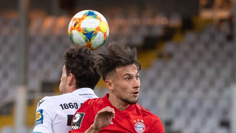 Zwei Fußballer - einer ganz in Rot, einer in Weiß und Dunkelblau – steigen Rücken an Rücken zum Kopfball hoch