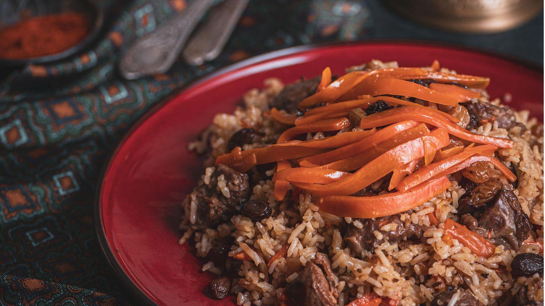 Qabuli Palau (Reis mit Lamm, Karotten und Rosinen)      Zutaten:   500 g Sella-Reis (im afghanischen Supermarkt oder online erhältlich), 1 kg Lammfleisch aus der Keule mit Knochen (vom Metzger in 5 cm große Würfel schneiden lassen), 3 Zwiebeln, Pflanzenöl zum Anbraten, 2–3 TL Char Masala oder Garam Masala, 1 TL Kardamompulver, frisch gemahlener schwarzer Pfeffer, Salz, 200 g Rosinen, 4 Bio-Karotten (insgesamt 400 g), 4 TL Zucker      Zubereitung:  1. Den Reis mit Wasser bedecken und 1–2 Stunden quellen lassen. Anschließend abgießen und abtropfen lassen.  2. Das Lammfleisch trockentupfen. Die Zwiebeln abziehen und in feine Würfel schneiden. Etwas Öl in einem Schnellkochtopf erhitzen und das Fleisch darin rundherum kräftig anbraten. Dann die Zwiebeln dazugeben und langsam goldbraun schmoren. Die Mischung mit dem Char oder Garam Masala, dem Kardamompulver, Pfeffer und Salz würzen. 750 ml Wasser angießen und das Lamm im fest verschlossenen Schnellkochtopf 20 Minuten garen. (Bei Zubereitung in einem normalen Topf beträgt die Garzeit 60–90 Minuten.)  3. In der Zwischenzeit bei Bedarf die Rosinen entstielen. Die Karotten waschen, putzen und zunächst längs in dünne Scheiben und dann in schmale Streifen schneiden. Etwas Öl in einer Pfanne erhitzen. Die Rosinen darin unter ständigem Rühren so lange braten, bis sie prall und rund geworden sind. Anschließend herausnehmen und beiseitestellen. Die Karotten in derselben Pfanne etwa 3–4 Minuten anbraten. Zuletzt den Zucker unterrühren und die Karotten 2 Minuten karamellisieren. Anschließend herausnehmen und zusammen mit den Rosinen bis zum Anrichten beiseitestellen.  4. Nach Ende der Garzeit des Lamms am Schnellkochtopf den Druck ablassen. Den Schnellkochtopf öffnen, das Fleisch aus dem Sud heben und abgedeckt warm halten. Den Sud durch ein feines Sieb in einen großen Topf streichen und kurz aufkochen. Dann den Reis zum Sud geben. Bei aufgesetztem Deckel bei mittlerer Temperatur so lange garen, bis die Flüssigkeit vom Reis komplett