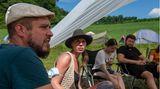 Stuhlkreis auf Klappstühlen: Die Veranstalter Nils (l) und Sandra (2.v.l) diskutieren in einer Gemeinschaftsrunde unter dem Sonnenschutz.