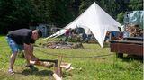 Erik hackt vor dem Gemeinschaftszelt Feuerholz für das Lagerfeuer am Abend
