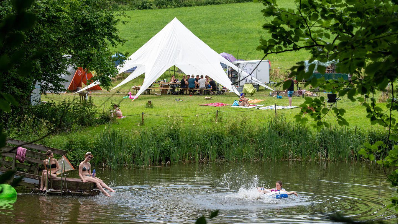 Bild 1 von 9 der Fotostrecke zum Klicken: Teilnehmer eines Ferienlagers in Rosenberg in Baden-Württemberg schwimmen in einem See, während die anderen zusammen im Gemeinschaftszelt sitzen.