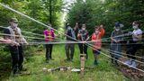 Jetzt müssen die Teilnehmer der Schnitzeljagd gemeinsam eine Aufgabe zu lösen, bei der Holzteile mit einem Netz bewegt werden.