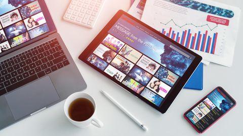 Tablet oder Laptop: Ein Tablet liegt rechts von einem Laptop auf dem Schreibtisch.