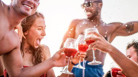 Junge Leute in Badekleidung stoßen mit Getränken an