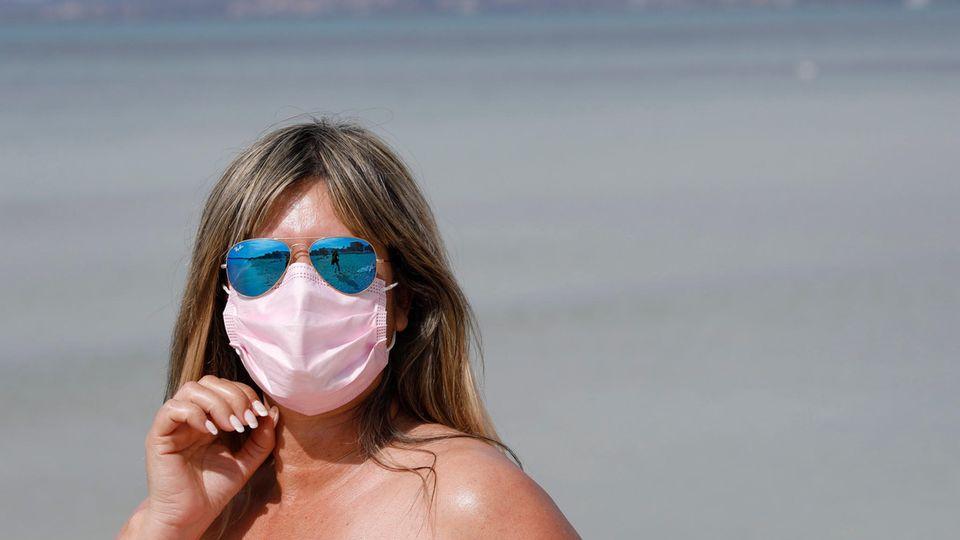 Eine weiße Frau mit langen, dunkelblonden Haaren trägt am Strand eine verspiegelte Piloten-Sonnenbrille und eine OP-Maske