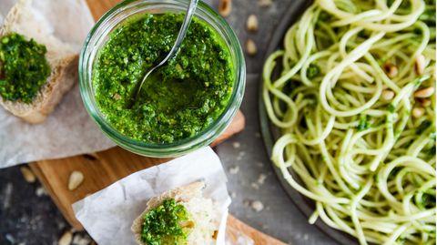 Ein Glas mit grünem Peste neben einem Teller Spaghetti