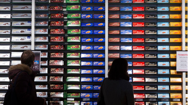 Menschen stehen vor einem großen Verkaufsregal mit Schokolade