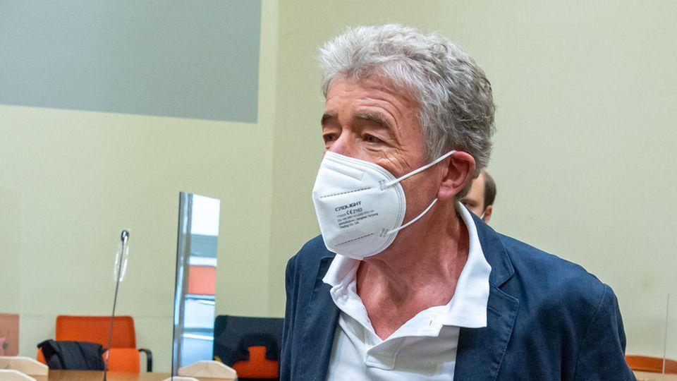 Ein älterer Mann mit weißem Bürstenschnitt und blauem Anzug steht mit FFP2-Maske in einem Gerichtssaal