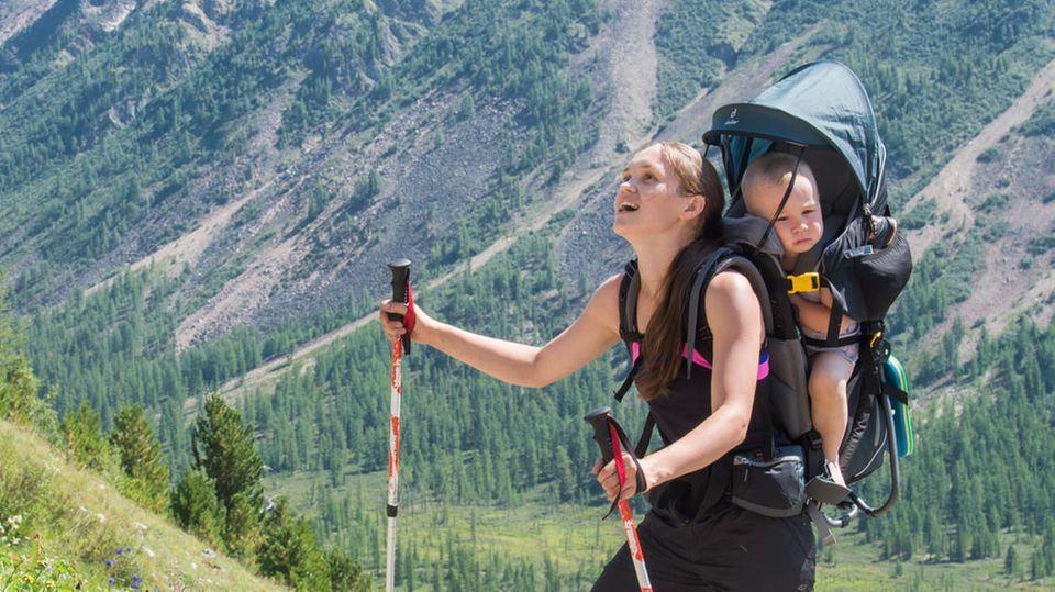 Mit Kind und Kraxe: Junge Frau verschnauft mit ihrem Kind in der Kraxe an einem Berg