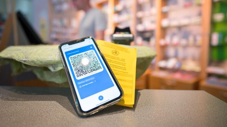Ein Smartphone mit dem QR Code eines digitalen Impfausweises liegt auf dem Tisch einer Apotheke