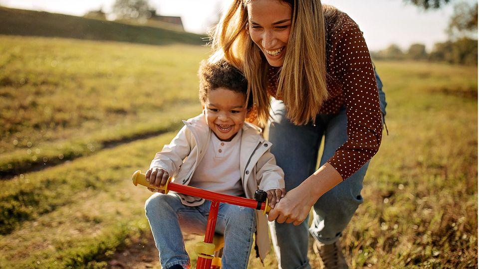 Mutter bringt ihrem Sohn auf einer Wiese das Fahrradfahren bei