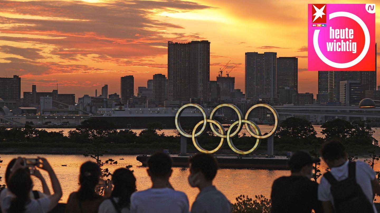 Menschen schauen auf die bei Sonnenuntergang beleuchteten olympischen Ringe in der Bucht von Tokio