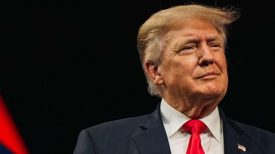 Milde lächelnd steht Donald Trump in Anzug und mit typischer roter Krawatte an einem Rednerpult vor dunklem Hintergrund